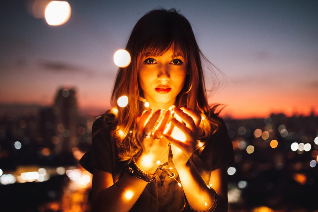 pretty girl glowing with light-bulbs wrapped around her palms