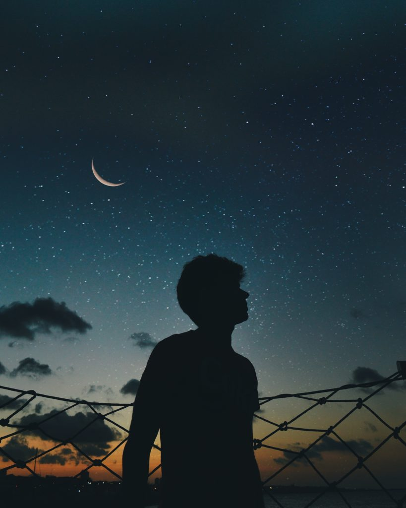 lonely man looking at the dark sky