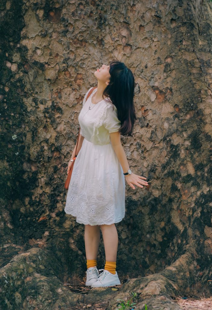 a beautiful girl wearing white dress looking upwards